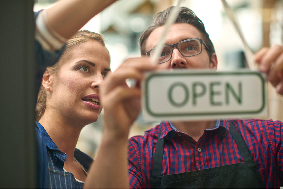 A man and a woman turning a sign to open