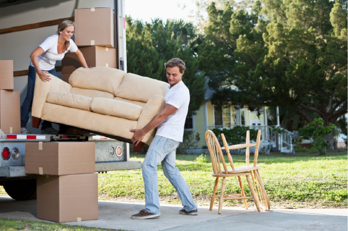 Man and a woman moving a couch into a moving truck