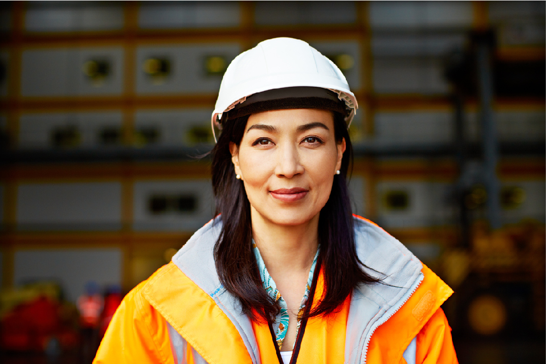 A women in a construction outfit smiling